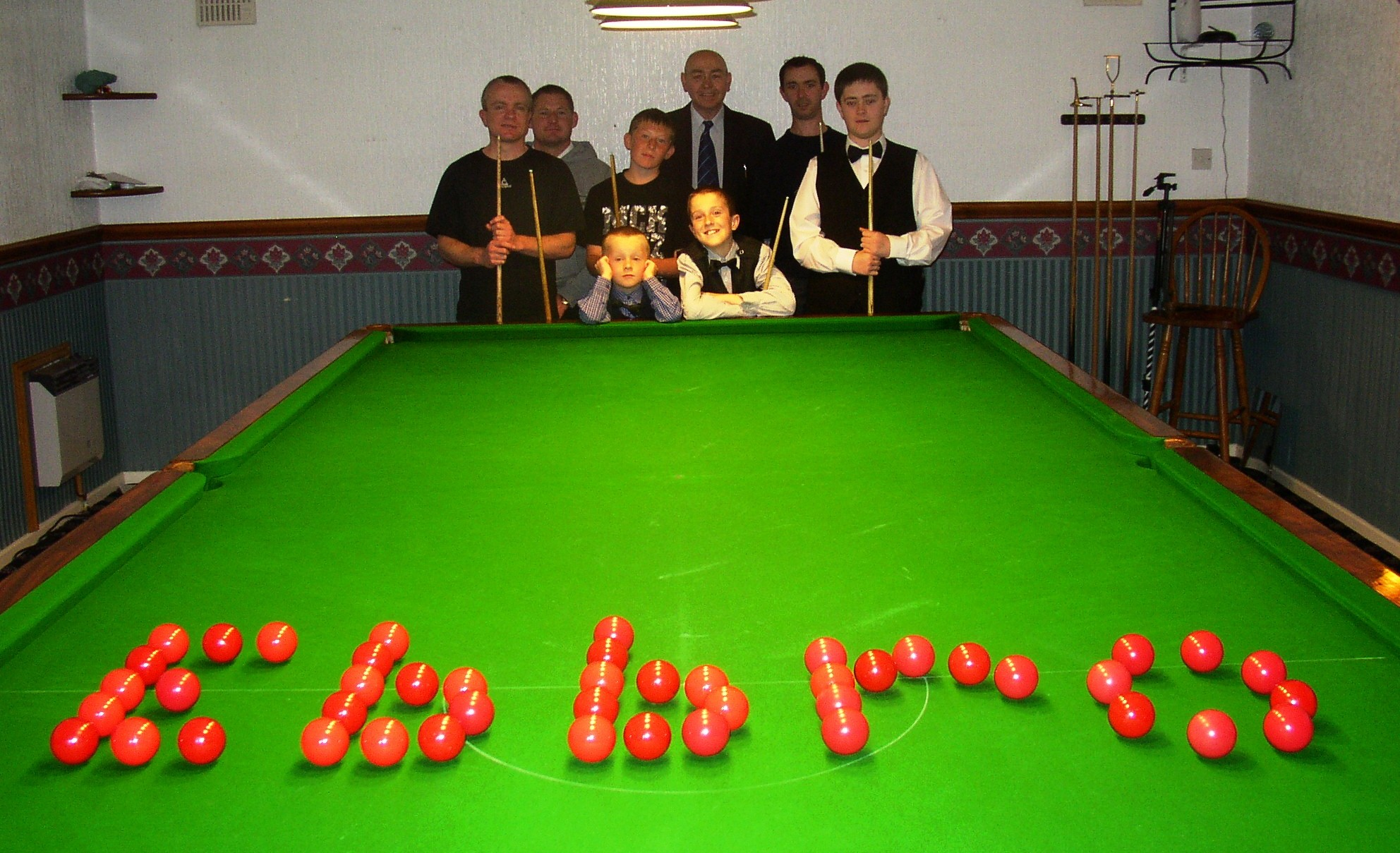 Academy members standing around a snooker table